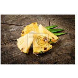 Naklejka Ananas. Plastry odizolowane na drewnianym tle.